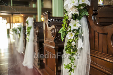 Wedding Decoration White Flowers And Green Leafs Hanging On The Church Benches Stock Photo