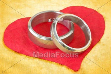 Wedding Rings On The Red Crumpled Paper Heart Stock Photo