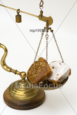 Weighing sweet rolls on an old brass scale Stock Photo