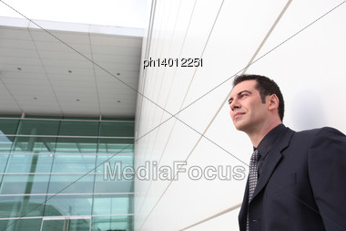 Well Dressed Man Leaning Against A Modern Building Stock Photo
