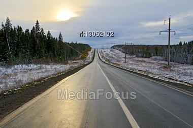 Wet Asphalt Road, Forest, Snow And Sun Beam On A Dark Gloomy Sky Stock Photo