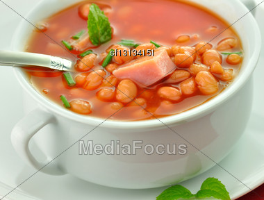 White Bean Soup With Ham And Tomatoes In A White Soup Cup Stock Photo