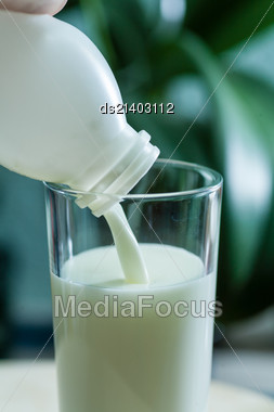 White Bottle And Milk Poured In Glass Cup Over Indoors Background Stock Photo