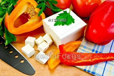 White Brine Cheese, Black Knife, Parsley, Tomatoes, Red And Yellow Bell Pepper, Napkin On A Wooden Board Stock Photo