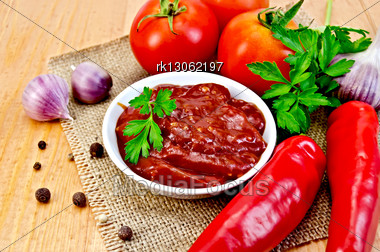 White Cup Ketchup, Tomatoes, Two Red Fresh Chilli Peppers, Garlic, Peppercorns, Mustard, Parsley Against Burlap Cloth And Wooden Board Stock Photo