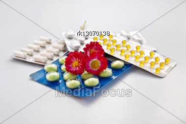 White And Green Pills, Capsules Yellow Packages With Three Daisies Isolated On Gray Background Stock Photo