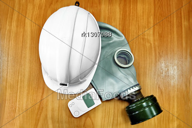 White Helmet, Gas Mask And A Dosimeter On The Background Of A Wooden Tabletop Stock Photo