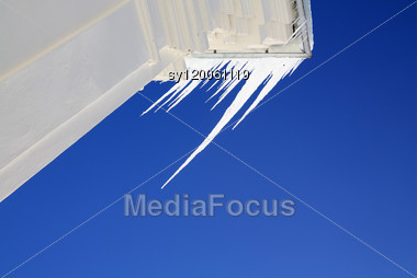 White Icicles On Blue Background Stock Photo