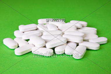 White Medical Pills On The Green Background Stock Photo