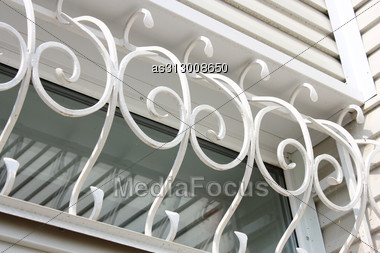 White Metal Forged Carved Lattice At A Plastic White Window Stock Photo