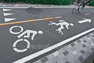 White Painted Signs For Bike And Rollerblades Line, Bicyclist In Motion Blur On A Bike Path Stock Photo