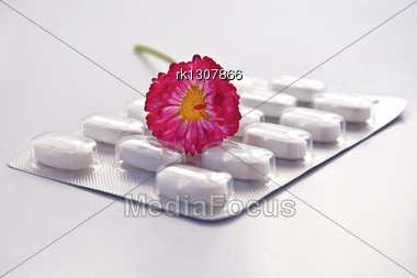 White Round Pill In A Package With Daisy Isolated On Gray Background Stock Photo