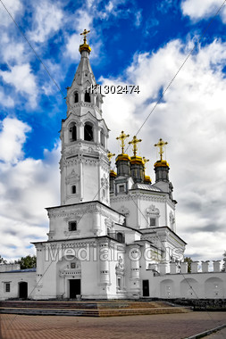 White Stone Holy Trinity Church Tower With Gold Baths And Crosses Against The Blue Sky, White Clouds (Verhoturie City Of Sverdlovsk Region) Stock Photo