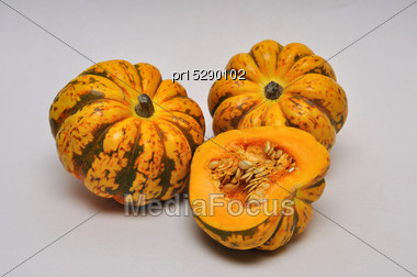 Whole And Sliced Pumpkins On A Seamless Background Stock Photo