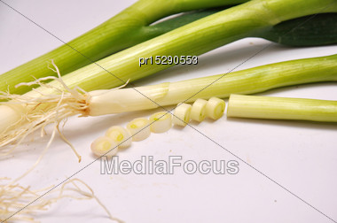 Whole And Sliced Spring Onions On A Seamless Background Stock Photo