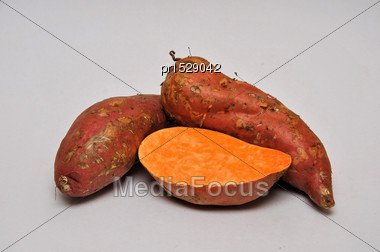 Whole And Sliced Sweet Potatoes On A Seamless Background Stock Photo