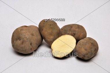 Whole And Sliced Unwashed Potatoes On A Seamless Background Stock Photo