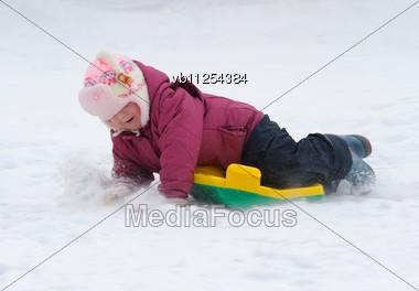 Winter Games Children - A Girl Sledding Down The Hills Stock Photo