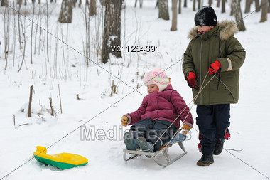 Winter Games Children - A Girl On A Sledge And A Boy Next Stock Photo