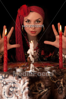 Witch At The Table With Candles. Stock Photo