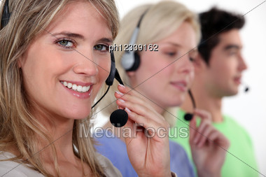 Woman And Colleagues Wearing Headsets Stock Photo