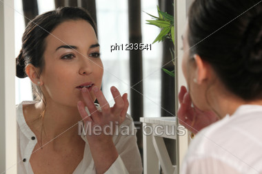 Woman Applying Lip Gloss Stock Photo