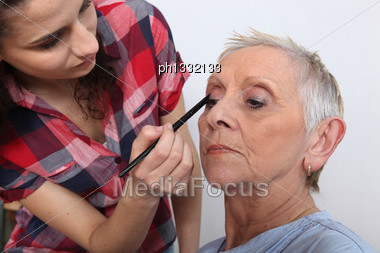 Woman Applying Makeup To An Older Lady Stock Photo