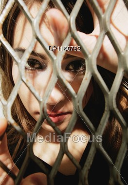 Woman Behind A Fence Stock Photo