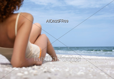 Woman In Bikini Pants And Shirt Laying In The Sand Looking Out To The Ocean Stock Photo