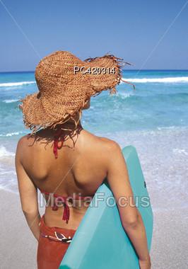 Woman In Bikini & Straw Hat Looking At The Water Stock Photo