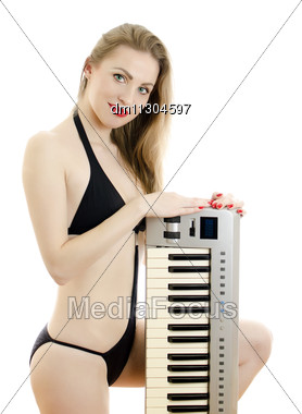 Woman In Black Swimsuit Posing With Piano Keyboard. Isolated On White. Stock Photo