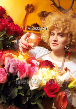 Woman With Blond Curls In Flower Shop Stock Photo
