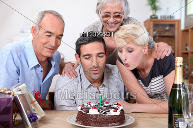 Woman Blowing Birthday Candles In Family Stock Photo