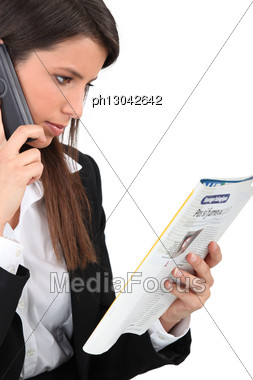 Woman Calling An Advert In A Magazine Stock Photo