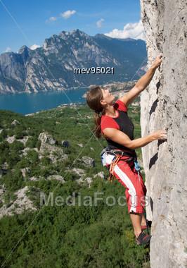 Woman Climbs On Rock Wall Stock Photo