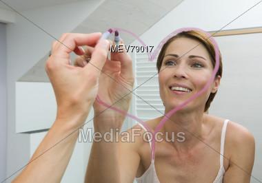 Woman Drawing Lipstick Heart on Mirror Stock Photo