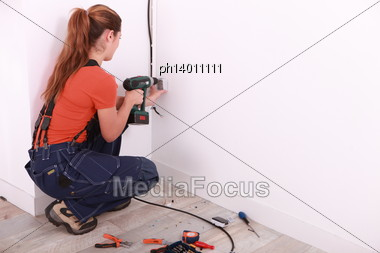 Woman Drilling Hole In Wall Stock Photo