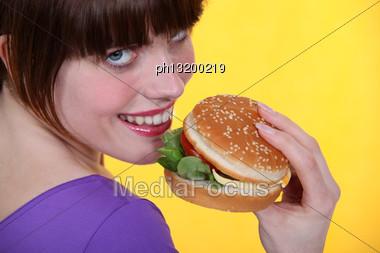 Woman Eating A Hamburger Stock Photo