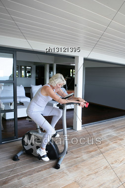 Woman Exercising On A Stationary Bicycle Stock Photo