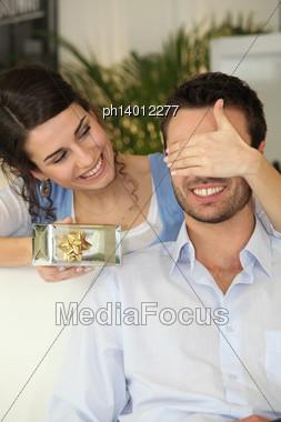 Woman Giving Gift To Boyfriend Stock Photo