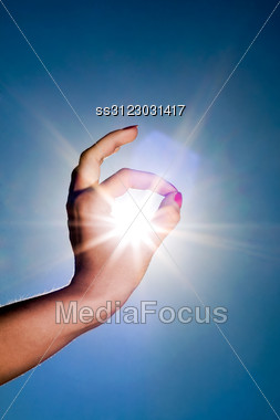 Woman Hand Around The Sun And Blue Sky Stock Photo