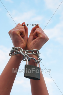 Woman's Hands Tied Up With Chains Against Blue Sky Stock Photo