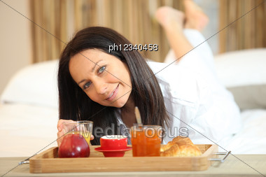 Woman Having Breakfast In Bed Stock Photo