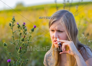 Woman With Hay Fever Spraying Nasal Drops To Help Respiration Stock Photo