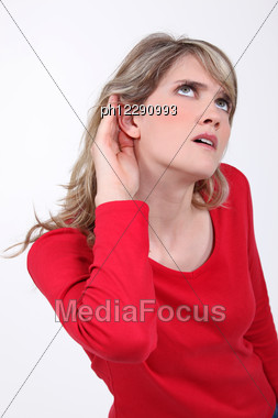 Woman With Her Hand To Her Ear Stock Photo