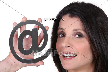 Woman Holding An @ Sign Stock Photo