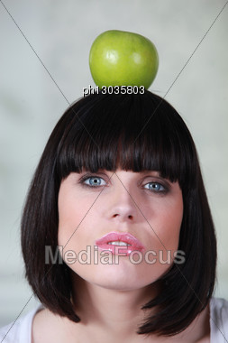Woman Holding An Apple On Her Head Stock Photo