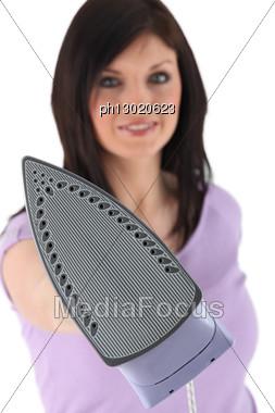 Woman Holding Iron At Camera, Brunette Stock Photo