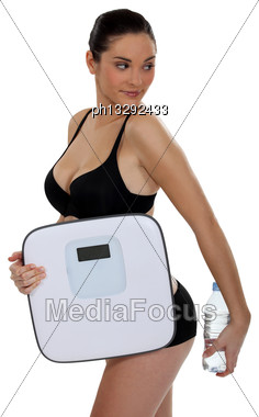 Woman Holding A Scale And A Bottle Of Water Stock Photo