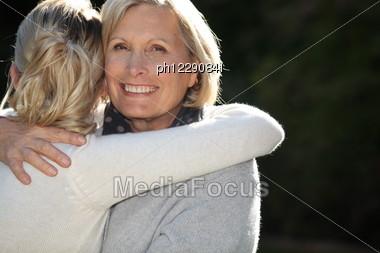 Woman Hugging Her Granddaughter Stock Photo